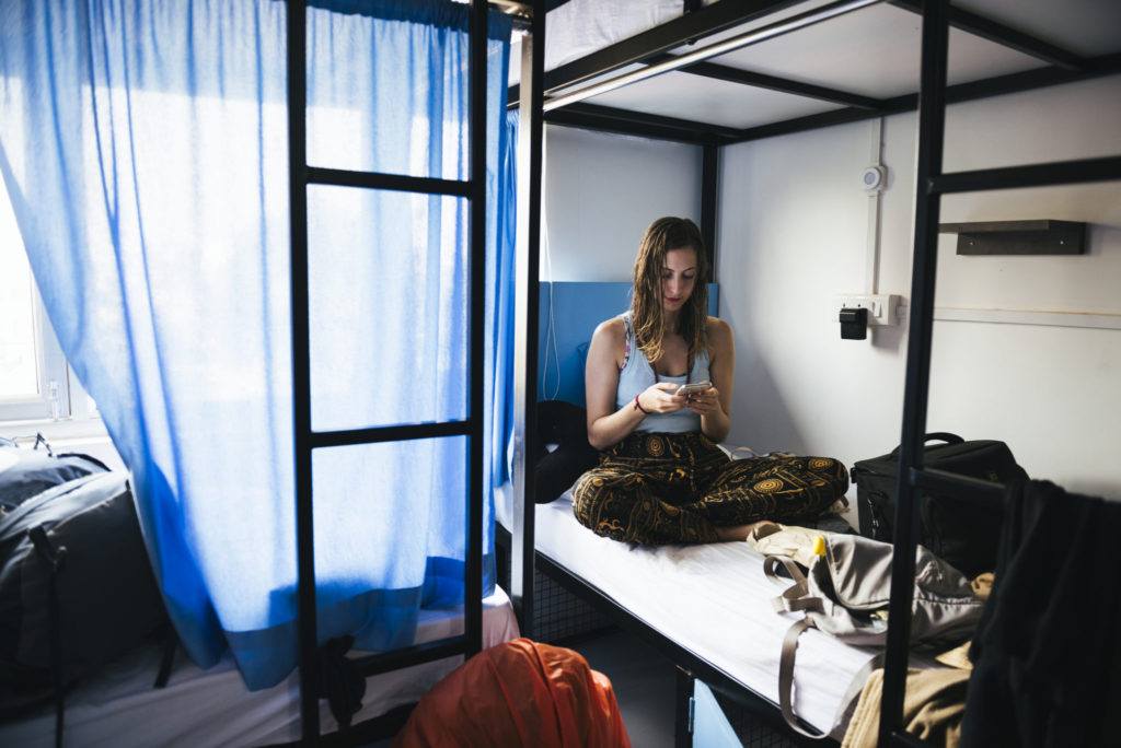 backpacker-using-her-phone-hostel-varanasi-india